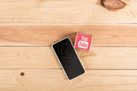 Photo for Top view of youtube icon and smartphone with blank screen on wooden table - Royalty Free Image