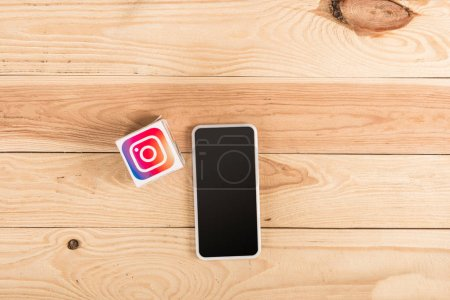 Photo for Top view of instagram icon and smartphone with blank screen on wooden table - Royalty Free Image