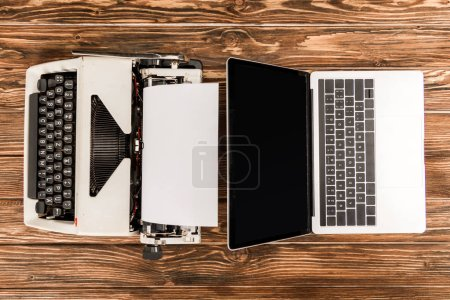 Photo for Top view of typewriter and laptop with blank screen on wooden table - Royalty Free Image