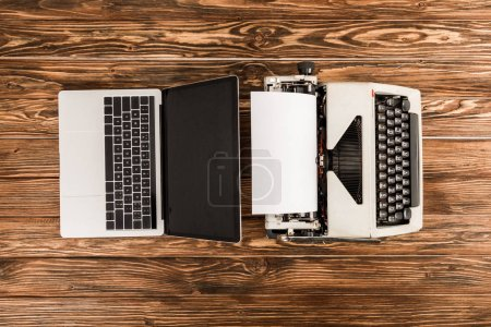 top view of typewriter and laptop on wooden table