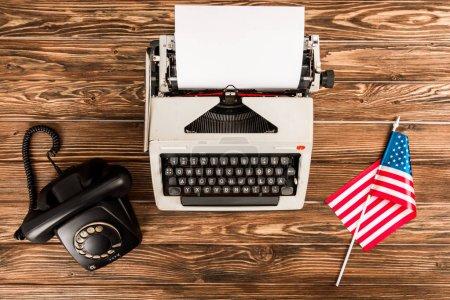 Photo pour Vue de dessus de la machine à écrire, rotatif cadran téléphonique et drapeau américain sur table en bois - image libre de droit