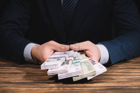 cropped shot of businessman holding russian rubles banknotes above wooden table