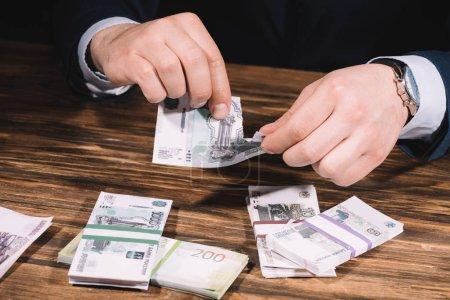 Photo pour Plan recadré de l'homme d'affaires déchirant billet au-dessus de la table en bois avec des roubles russes - image libre de droit