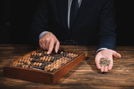 Photo for Cropped shot of businessman holding coins and using abacus at wooden table - Royalty Free Image