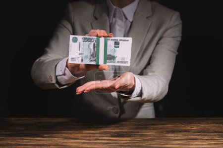 mid section of businesswoman sitting at wooden table and holding russian rubles banknotes on black