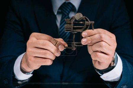 Photo pour Plan recadré de l'homme d'affaires tenant outil étau de fer avec pièce de monnaie en rouble russe - image libre de droit