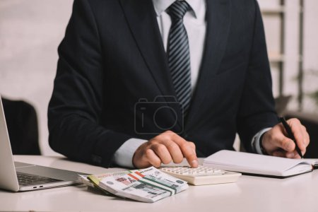 Photo for Cropped shot of businessman using calculator and taking notes in notepad at workplace with laptop and russian rubles banknotes - Royalty Free Image