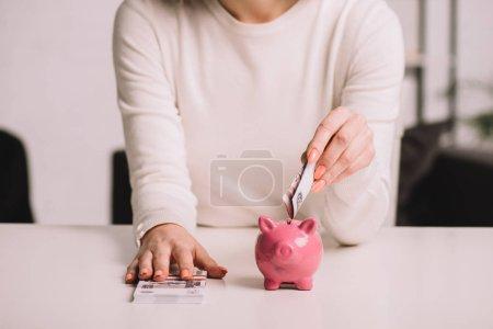 Mittelteil der Frau legt russische Rubel in Sparschwein, Sparkonzept