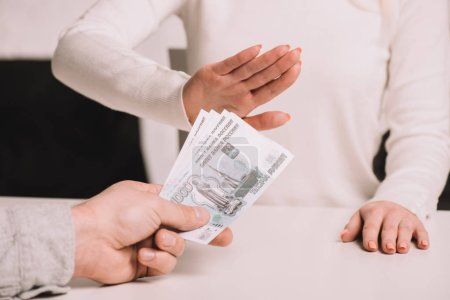 Photo for Cropped shot of man giving rubles banknotes to woman gesturing no sign - Royalty Free Image