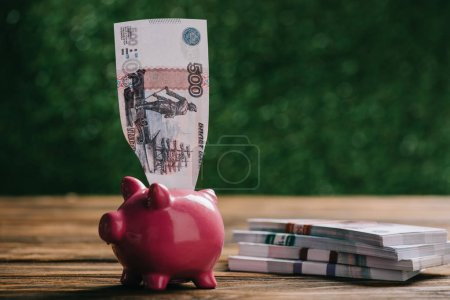 Photo for Close-up view of piggy bank with banknote and russian rubles on wooden table - Royalty Free Image