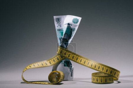 Photo for Close-up view of russian rubles banknote with measuring tape on grey - Royalty Free Image