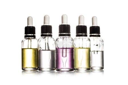Foto de Disparo de estudio de botellas cosméticas con colorido líquido aislado en blanco - Imagen libre de derechos