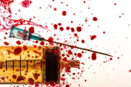 Photo pour Photo de studio de seringue, aiguille et le sang éclabousse - image libre de droit
