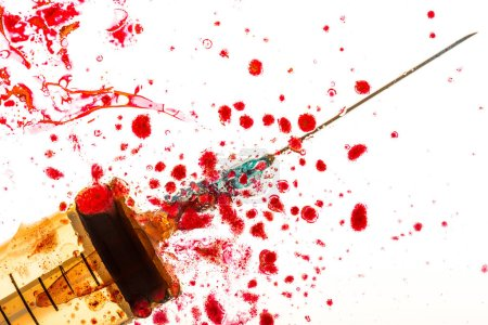 Close up view of syringe and blood on white