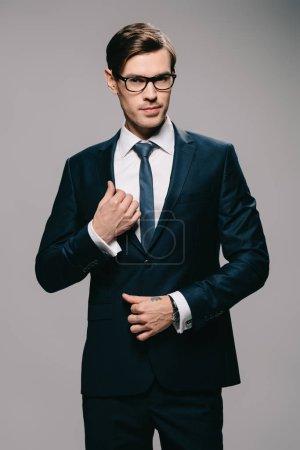 Photo pour Bel homme d'affaires touchant la veste sur fond gris - image libre de droit