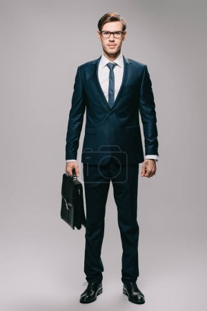 Photo for Confident businessman in suit holding briefcase on grey background - Royalty Free Image