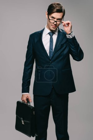 Photo pour Homme d'affaires en costume tenant porte-documents et toucher les verres sur fond gris - image libre de droit