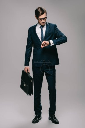 businessman holding briefcase and looking at watch on grey background