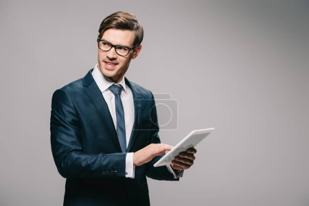 Photo for Cheerful businessman in glasses using digital tablet isolated on grey - Royalty Free Image