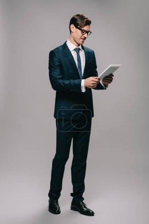 Foto de Empresario alegre en vasos con tableta digital aislada en gris - Imagen libre de derechos