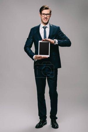 Photo pour Homme d'affaires joyeux tenant tablette numérique avec écran blanc sur fond gris - image libre de droit