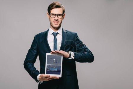 Photo pour Gai homme tenant une tablette numérique avec app tumblr sur écran isolé sur fond gris - image libre de droit
