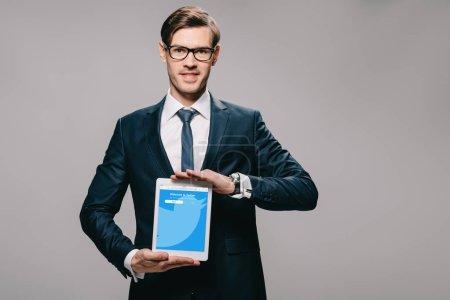 Photo pour Gai homme tenant une tablette numérique avec twitter app sur écran isolé sur fond gris - image libre de droit