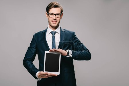 cheerful businessman holding digital tablet with blank screen isolated on grey