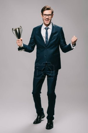 Photo for Handsome businessman celebrating victory and holding trophy in hand on grey background - Royalty Free Image
