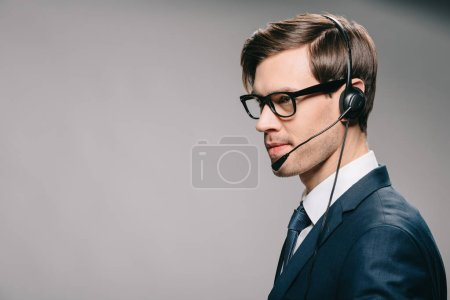 handsome man in suit and glasses wearing headset on grey background