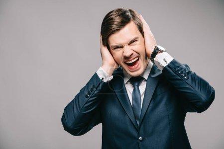 Photo pour Bel homme d'affaires couvrant les oreilles avec les mains et criant sur fond gris - image libre de droit