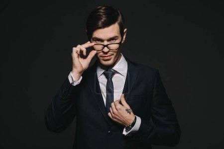 Photo pour Beau homme d'affaires touchant des lunettes tout en se tenant en costume isolé sur noir - image libre de droit