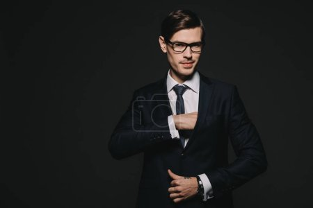 confident businessman putting hand in pocket in jacket isolated on black