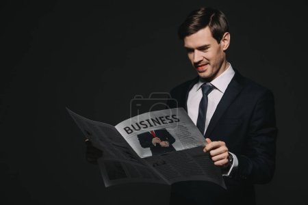 Photo for Cheerful businessman reading business newspaper isolated on black - Royalty Free Image