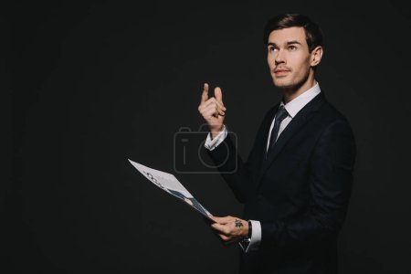 Photo for Pensive businessman holding business newspaper isolated on black - Royalty Free Image