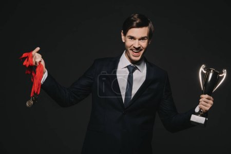 Photo for Happy businessman wearing medals and celebrating victory while holding trophy isolated on black - Royalty Free Image