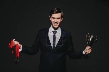 Photo pour Homme d'affaires souriant tenant trophée médailles dans les mains isolées sur noir - image libre de droit