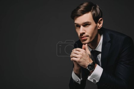 Photo for Pensive businessman in suit thinking isolated on black - Royalty Free Image