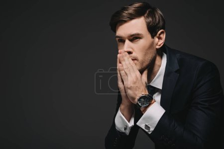 Photo for Pensive businessman with watch on hand thinking isolated on black - Royalty Free Image