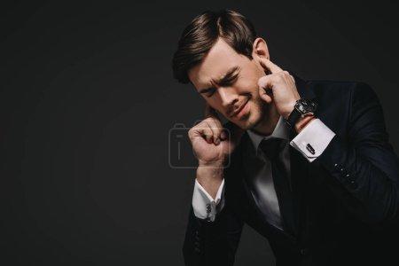 Photo pour Homme d'affaires brancher les doigts dans les oreilles isolées sur fond noir - image libre de droit