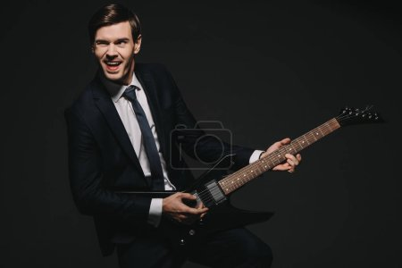 Photo for Cheerful businessman playing elecrtonic guitar isolated on black - Royalty Free Image