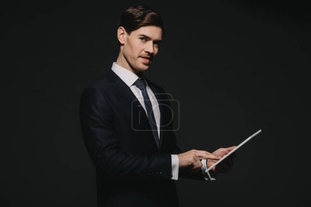 Photo for Cheerful businessman holding digital tablet in hands isolated on black - Royalty Free Image