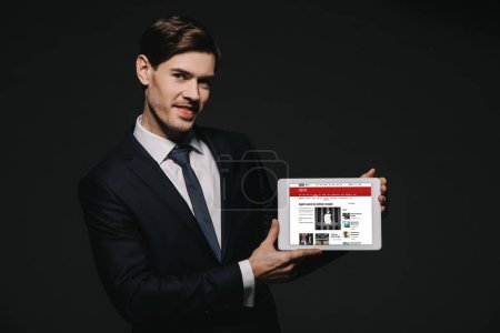 Photo for Cheerful businessman holding digital tablet with bbc news app in screen isolated on black - Royalty Free Image