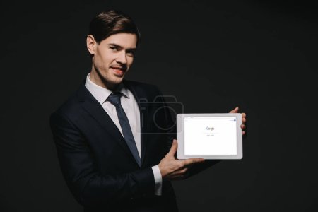 cheerful businessman holding digital tablet