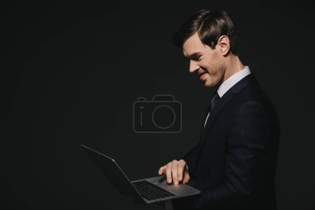 Photo for Handsome businessman using laptop isolated on black - Royalty Free Image