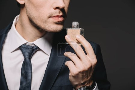 Photo for Cropped view of businessman smelling perfume isolated on black - Royalty Free Image