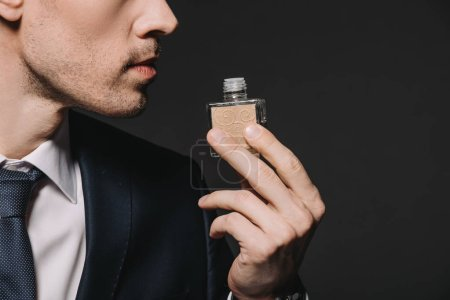 Photo for Cropped view of man in suit smelling perfume isolated on black - Royalty Free Image