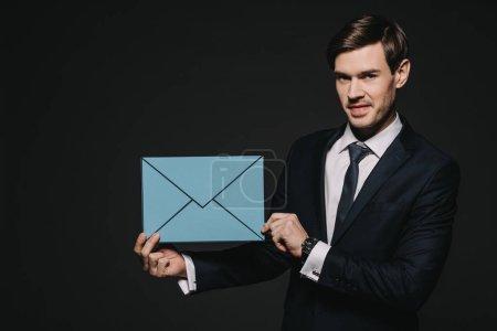 Photo pour Bel homme d'affaires tenue bleue enveloppe isolée sur fond noir - image libre de droit