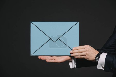 Photo for Cropped view of man holding blue envelope isolated on black - Royalty Free Image