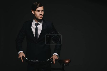 handsome businessman in suit holding bicycle isolated on black